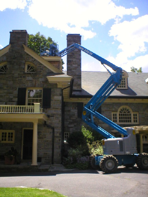 A Cherry Picker being used to repair & refurbish a stone chimney by W.S. Montgomery Chimney and Masonry Services in Cheltenham, PA 19012